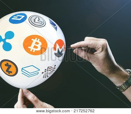 crypto currency concept - bit coin BTC the new virtual money on balloon with needle in hand before burst