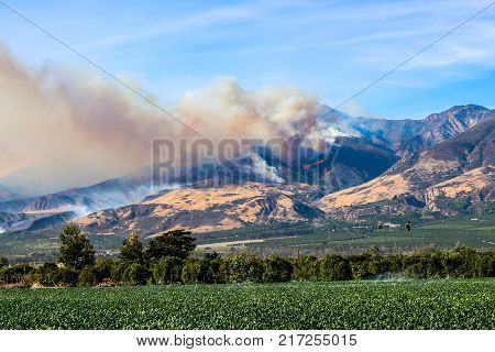 Helicopters fight wildfire burning in California mountains.  This is the Thomas fire burning in Ventura, California