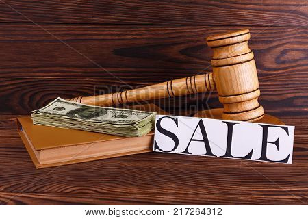 On a wooden background there is a wooden auctioneer's hammer, a brown notepad on which a stack of dollar bills and a sign with an inscription on sale. Side view.