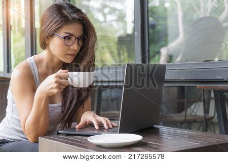 Casual business woman working on laptop. Young girl using computer outdoor drinking coffee in cafe. beautiful female with glasses sitting in coffee shop and working on notebook. Lady lifestyle.