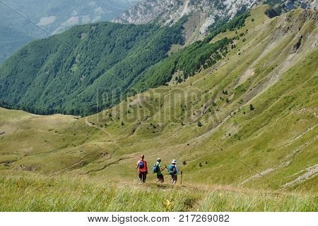 three hikers are heading to bottom of a valley between Montenegro Mountains