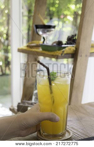 Woman hand on orange juice at table stock photo