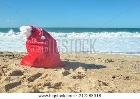 Christmas at the beach, red Santa bag with presents in the sand on sunny day. Display, copy space