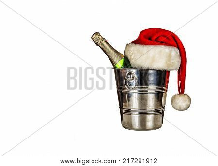 A bottle of champagne in an ice bucket and a Santa Claus hat isolated on white background. free place