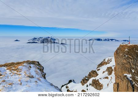Summits of the Swiss Alps rising from sea of fog - wintertime view from the Fronalpstock mountain in the Swiss canton of Schwyz.