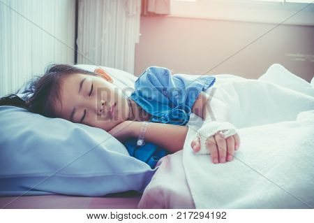 Illness asian child admitted in hospital with saline intravenous (IV) on hand. Girl sleeping at comfortable equipped hospital room with sunlight. Health care stories. Vintage film filter effect. poster