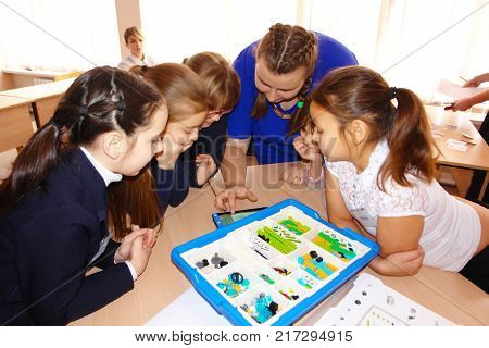 CHAPAEVSK, SAMARA REGION, RUSSIA - DECEMBER 07, 2017: Grammar school in city Chapaevsk. Schoolgirls in class are sitting at a desk. Before them a box with a Lego. SOFT FOCUS