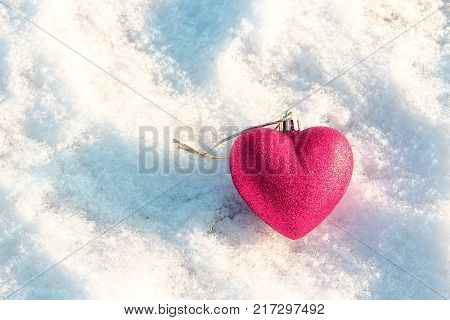 Red heart in the snow. The decoration on the Christmas tree. The spirit of Christmas. Christmas traditions. Winter mood and love. Heart on the snow. Valentine's day. Love and feelings