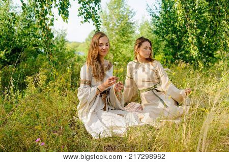 Attractive women in traditional russian clothes dreaming at nature background. Ivan Kupala Holiday Celebration