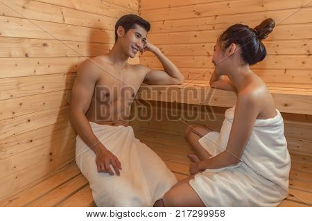 Beautiful couple relaxing in spa sauna room.