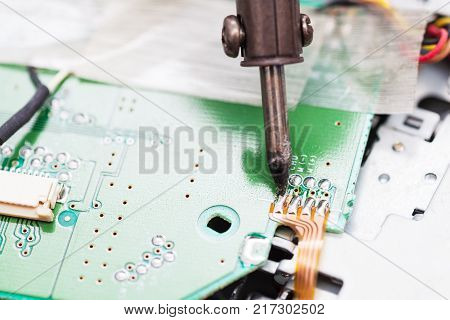 repairing of electric circuit board with soldering iron close up