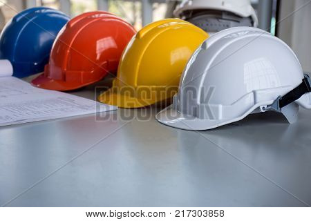 Blueprint and white, blue, red and yellow hard safety helmet hat on the table for safety project of architect, engineer or worker contraction equipment/concept of safety cooperation in work