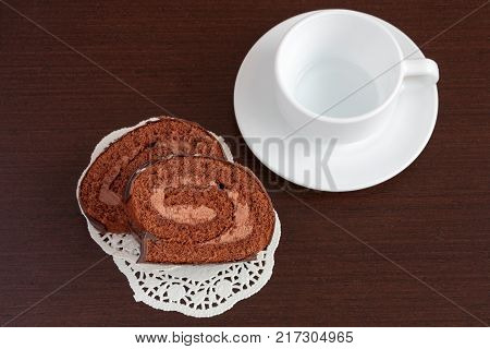 Chocolate sacher cake on wooden table with cup