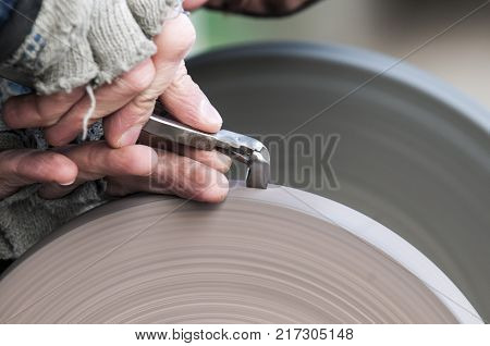 Master performs sharpening of dental tools on grinding wheels.