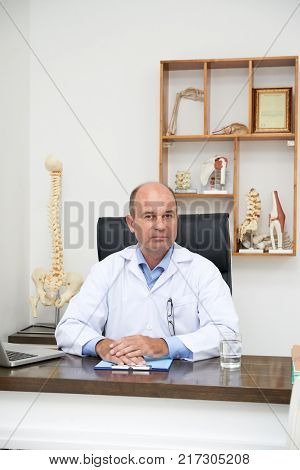 Portrait of professional osteopath at the table in his office