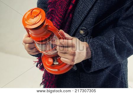 The girl in the grey coat and the scarf a crane holding a kerosene lamp in orange.