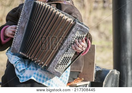 Playing outdoors on a big accordion. selective focus.