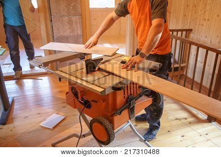 Worker using professional circular saw cutting click oak parquet. DIY professional work home improvement and renovation parquetry concept.