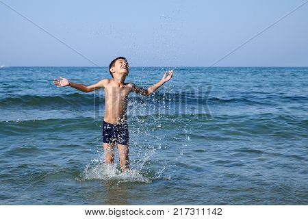Happy boy playing with water in blue sea