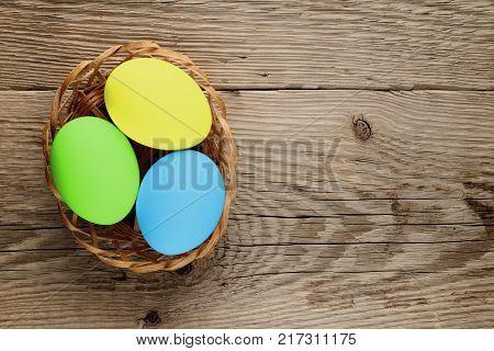 Easter eggs in basket on wooden background