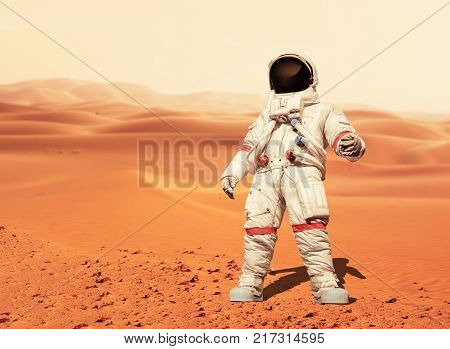 Man In A Space Suit Standing On The Red Planet Mars. Spaceman Conquer A New Planet. Concept Of The S