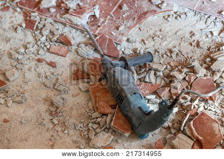Closeup photo of an electric industrial drilling equipment on demolished floor