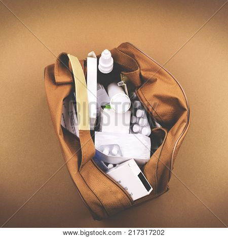 Brown bag with different drugs on a brown background.