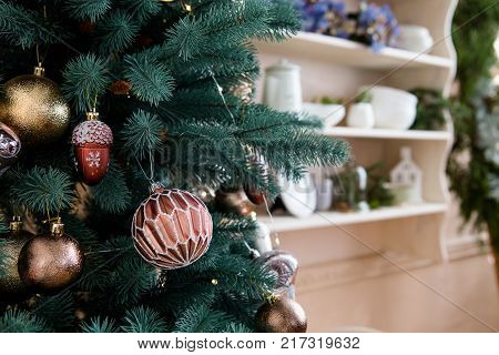 Christmass tree decoration close up shot. Winter holiday concept home inetior. Celebration New Year concept. Decorative christmass tree with kitchen shelf on background.