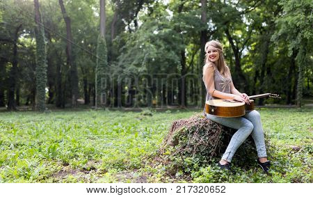 Beautiful hippie girl playing guitar in nature