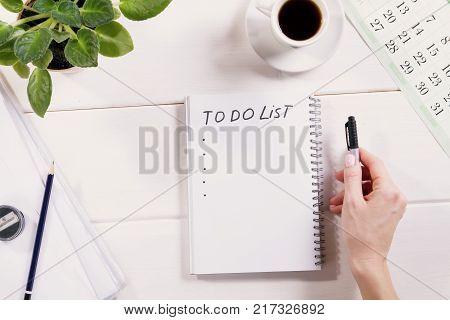 To do list written in a notebook . Notebook with an to do list on wooden desk with cup of coffee