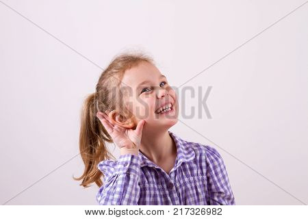 Beautiful smiling girl puts a hand to the ear to hear better. Young girl listening something over white background