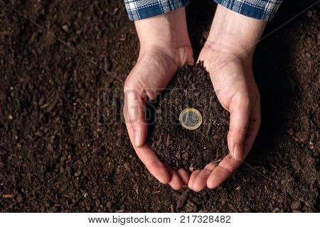 Making money from agricultural activity and earning extra income female farmer handful of soil with euro coin