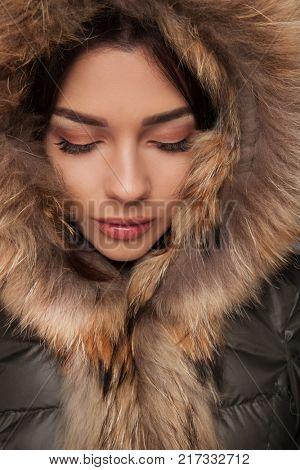 beautiful woman wearing fur hood looks down at something or he keeps her eye closed , studio picture
