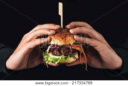 Hamburger burger with beef, carrot, cabbage and onion in man hands.