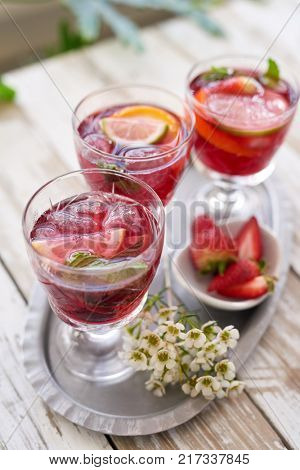 cold refreshing cocktails cranberry flavoured red wine sangria drinks for a spring summer party with fresh strawberries