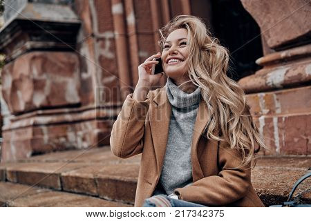 So good to hear you! Beautiful young woman talking on her smart phone and looking away with smile while sitting on stairs outdoors