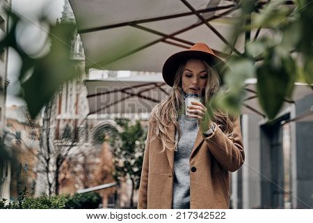 Enjoying hot coffee. Attractive young woman in hat and coat smelling coffee while standing outdoors