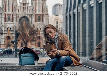 City life. Thoughtful young woman listening music using her smart phone and writing something down while spending carefree time in the city
