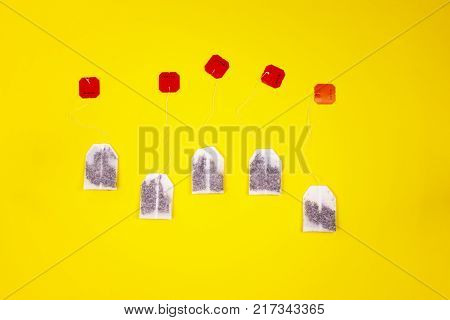 A set of teabags with black tea along the yellow background. Vivid concept of the tea party