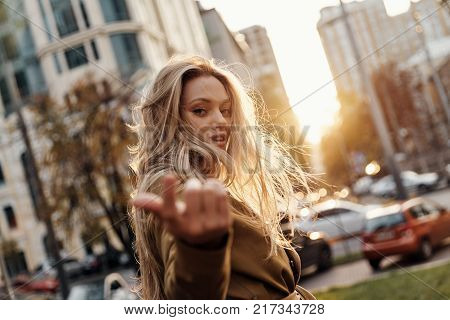 Irresistible girl. Attractive young smiling woman looking at camera and gesturing while standing outdoors