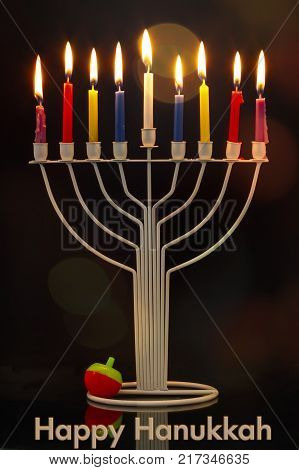 Happy Hanukkah jewish holiday. Menorah traditional candelabra with burning candles and Hanukkah Dreidel Sevivon against black background