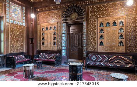 Cairo Egypt - December 2 2017: Manial Palace of Prince Mohammed Ali. Guests Hall with wooden ornate ceiling wooden ornate door lanterns colorful ornate couches tea tables and ornate carpet
