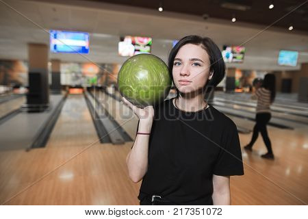 Pretty bowler with the blue ball. Beautiful young girl with green ball for bowling. The girl stands against the background of the bowling lanes and looks at the camera