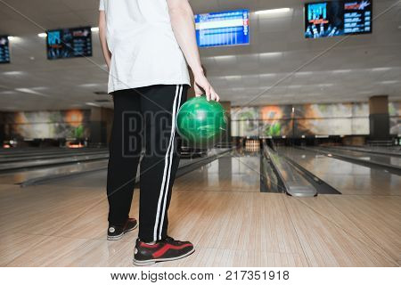 A man stands on a track for playing bowling with a ball in his hands and is about to make a throw. A man with a green bowling ball in his hands.