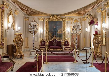 Cairo Egypt - December 2 2017: Throne Hall at Manial Palace of Prince Mohammed Ali Tewfik with gold plated red armchairs antique floor lamps ornate ceiling and red carpets