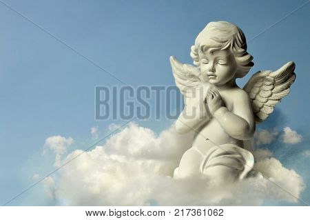 Angel guardian praying and kneeling on the cloud