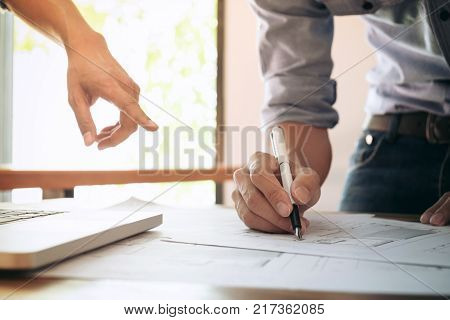 Image of engineer or architectural project engineering and partner drawing plan on BluePrint with Engineering tools on workplace.
