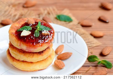 Cottage cheese pancakes with berry jam, almonds nuts and mint on a served plate. Healthy cottage cheese almond flour pancakes. Closeup