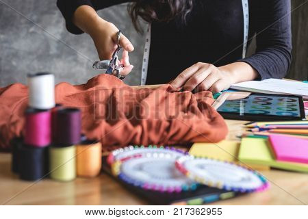 Young woman dressmaker or designer working as fashion designers measure and Cutting for clothes profession and job occupation Fashion Designer Stylish Concept. poster