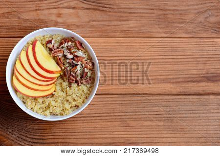 Quinoa with apples and pecan nuts. Breakfast quinoa porridge in a white bowl isolated on wooden background with copy space for text. Vegan sweet dish. Top view